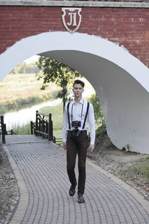 Stylishly dressed young man is walking in the park. In his hands holds a SLR film camera. Stock fotó