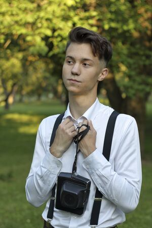 Stylishly dressed young man posing in a park. Laughing brings his hands to his chest. In the hands of the camera in a case. Stock fotó