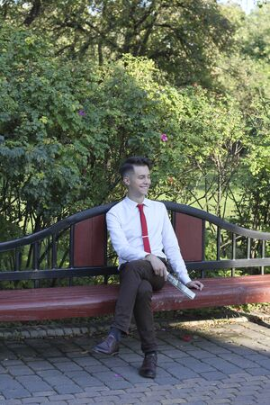 A stylishly dressed young man sits on a park bench and looks away with a smile. Stock fotó