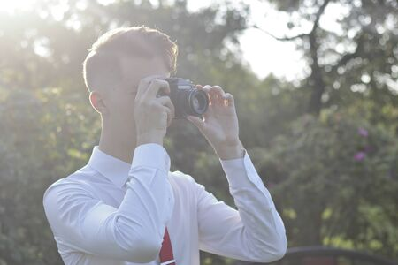 Stylishly dressed young man sits taking pictures in the park. In his hands holds a SLR film camera. Stock fotó