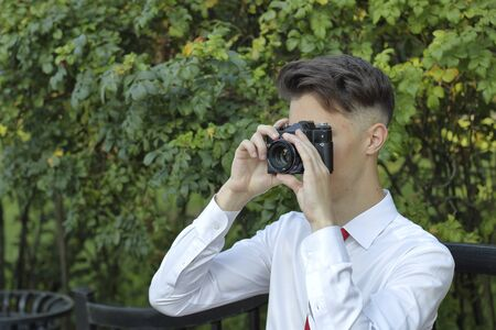 Stylishly dressed young man sits on a park bench and takes pictures. In his hands holds a SLR film camera. Stock fotó