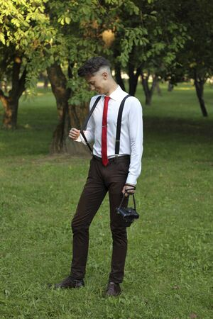 Stylishly dressed young man posing in a park. Pulls the gum from the urine. A SLR film camera hangs on his shoulder.