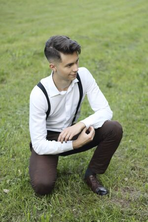Stylishly dressed young man posing in a park. Squatting on the lawn straightens the button on his shirt.