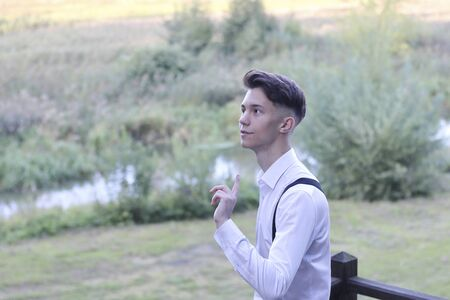 Stylishly dressed young man posing in a park. Raising a finger to the top, he listens warily. Stock fotó