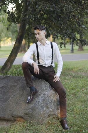 Stylishly dressed young man sits on a stone boulder in the park. With a thoughtful look.