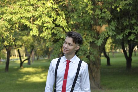 Stylishly dressed young man posing in a park.