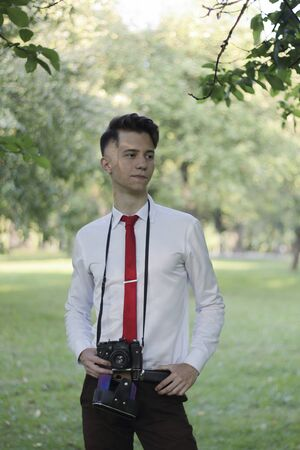 Stylishly dressed young man posing in a park. A SLR film camera hangs on the neck. Banque d'images - 130729844