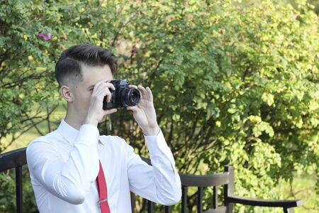 Stylishly dressed young man sits taking pictures in the park. In his hands holds a SLR film camera. Banque d'images - 130730114