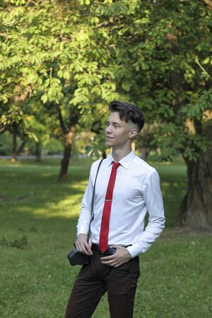 Stylishly dressed young man posing in a park. A SLR film camera hangs on his shoulder. Banque d'images - 130732796