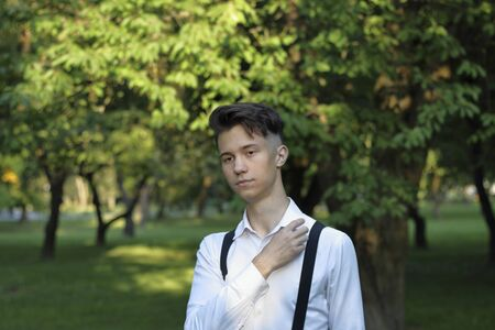 Stylishly dressed young man posing in a park. Looks thoughtfully to the side, straightens his shirt collar. Banque d'images - 130733461