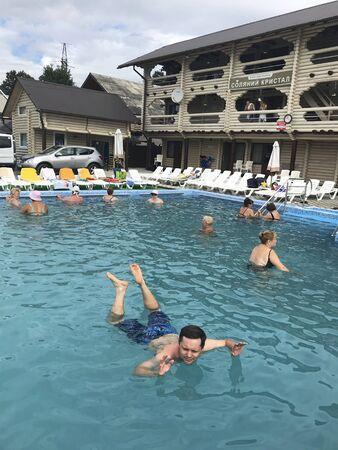 UKRAINE, SOLOTVINO, SEPTEMBER 3, 2019, Vacationers take water procedures in the salt water pool. Water keeps them on the surface. Salt Crystal Resort