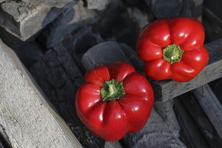 Ripe sweet peppers from the infield. Lies on wooden boards, bathed in sunlight. Stock fotó