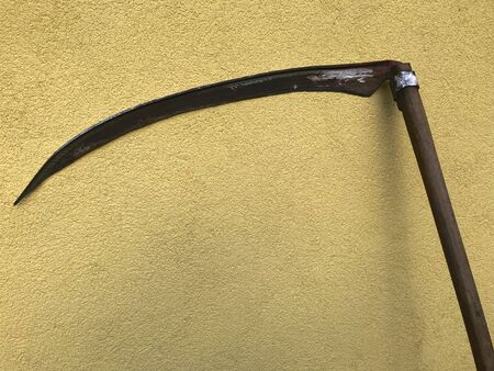 An old two-handed scythe for hay. It stands against a wall covered with stucco. The wall is painted yellow.