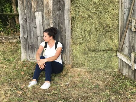 A girl with a backpack behind her. Sits by a wooden shed that is filled with hay. Stock fotó