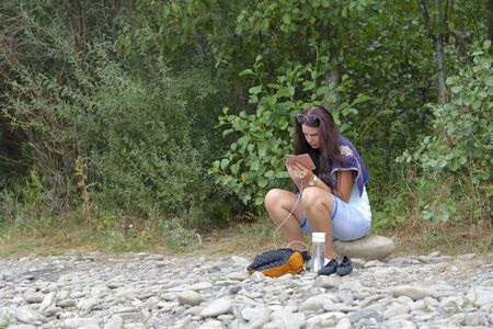 A girl sits on the shore of a mountain river and looks into a smartphone. Nearby travel supplies.