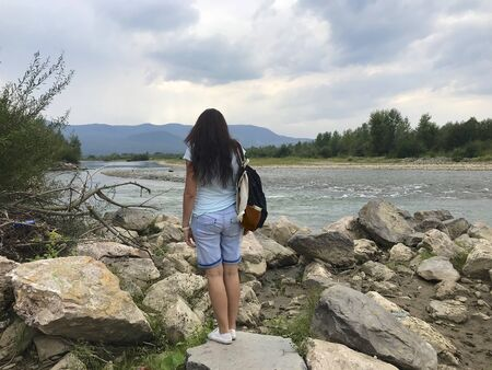 A girl with a backpack on his shoulder stands on a large boulder near a mountain river. Looks at the water stream. Far away on the horizon are mountains covered in haze.