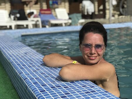 Girl in the pool outdoors. Leaned on board the pool. Smiling, sunglasses on his head.