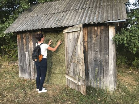 A girl with a backpack behind her. It stands by the wooden shed, which is filled with hay.