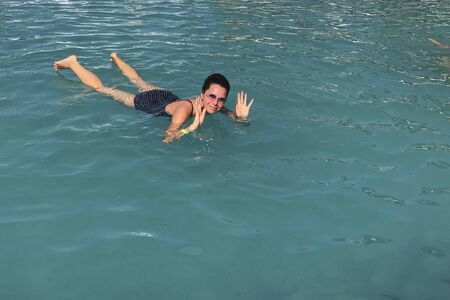 Girl in the pool outdoors. The salt water of the pool holds it on the surface of the water. Smiling, sunglasses on his head.
