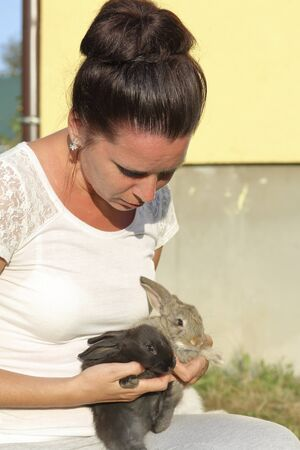 A woman holds a rabbits in her hands. Presses it to the chest. It stands in the courtyard of a private courtyard. Stock fotó