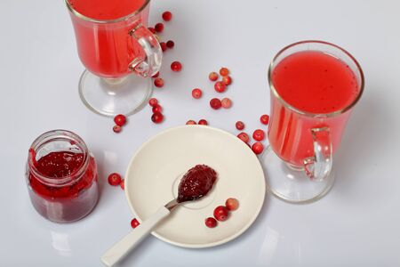 Homemade blanks. Cranberry jam in an open jar and glasses with cranberry juice. On a saucer is a teaspoon with jam. Several berries are scattered on the surface.