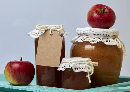 Homemade seasonal preparations. Beautifully packaged jars of apple jam. Covered with paper and tied with a cord. Nearby are fresh apples. Stock Photo