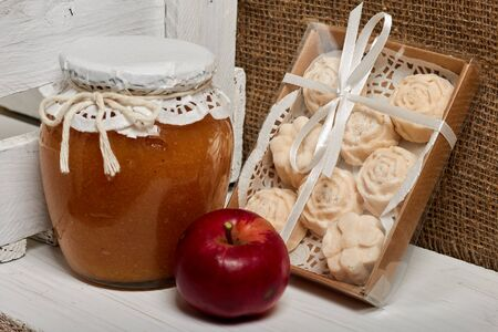 Homemade seasonal preparations. Beautifully packaged jars of apple jam. Covered with paper and tied with a cord. Next to fresh apples and apple marshmallow in the package. Stock Photo