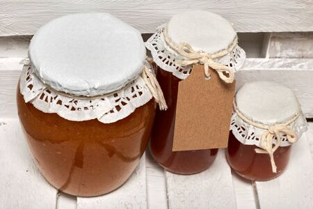 Homemade seasonal preparations. Beautifully packaged jars of apple jam. Covered with paper and tied with a cord. Stock Photo
