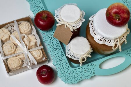 Homemade seasonal preparations. Beautifully packaged jars of apple jam. Covered with paper and tied with a cord. Next to fresh apples and apple marshmallow in the package. View from above. Stock Photo