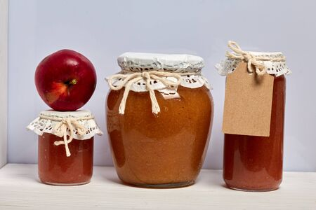 Homemade seasonal preparations. Beautifully packaged jars of apple jam. Covered with paper and tied with a cord. Nearby are fresh apples. 写真素材