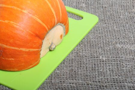 Half an orange pumpkin lies on a cutting board. The surface is covered with coarse linen cloth.