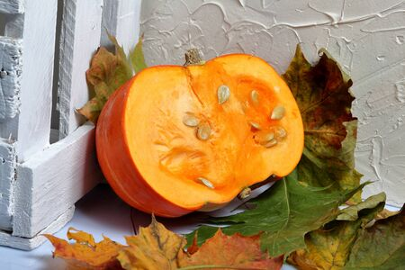 Half an orange pumpkin lies on a white surface. Nearby is a box of white painted wooden boards. Decorated with colorful autumn leaves. Stok Fotoğraf