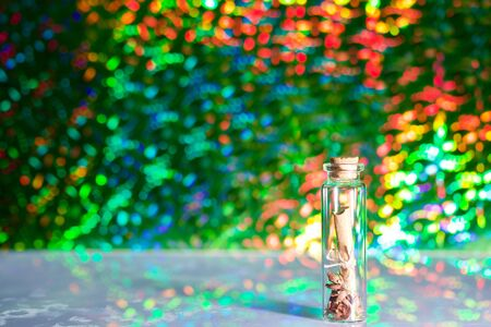A note folded into a tube lies in a glass bottle. Against the background of rainbow bokeh.