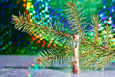 A note folded into a tube lies in a glass bottle. Against the background of a fir branch and rainbow bokeh.