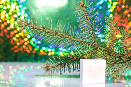 Cardboard boxes with gifts. Against the background of a fir branch and rainbow bokeh.