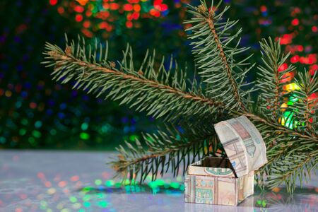Open chest with gifts. Against the background of a fir branch and rainbow bokeh. Stock Photo