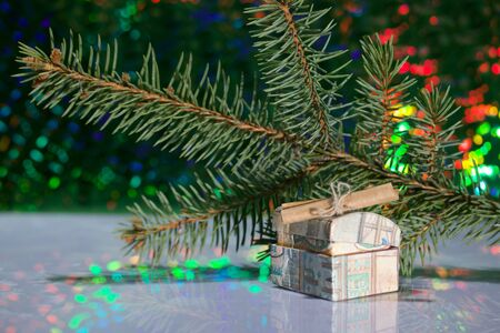 Open chest with gifts. A folded note is enclosed in it. Against the background of a fir branch and rainbow bokeh.