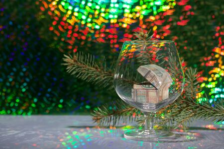 An open chest with gifts stands in a wine glass. Against the background of a fir branch and rainbow bokeh.