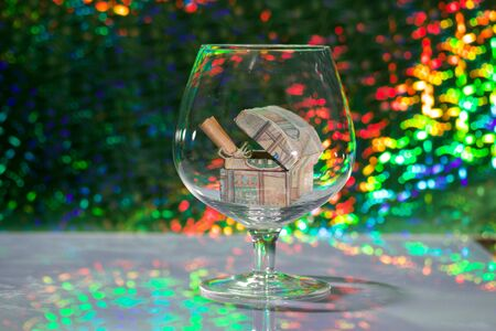 An open chest with gifts and a note folded into a tube. Stands in a wine glass. Against the background of a fir branch and rainbow bokeh.