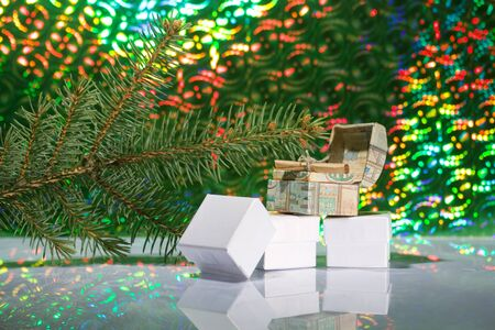 Cardboard boxes with gifts. One of them has a note. Against the background of a fir branch and rainbow bokeh. Stock Photo