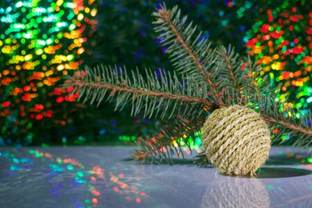 Decorative ball. Against the background of a fir branch and rainbow bokeh.