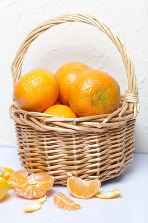 Tangerines in a wicker basket. Next to the basket is peeled mandarin. Visible slices of mandarin and skin from it. On white background. Stock Photo