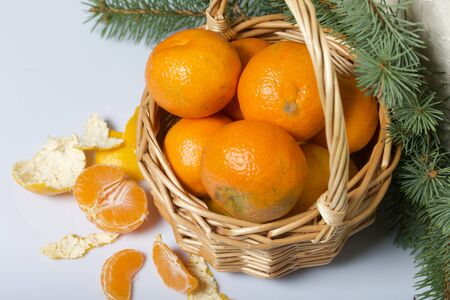 Tangerines in a wicker basket. Next to the basket is peeled mandarin. Visible slices of mandarin and skin from it. Branches of green spruce. On white background. Stock Photo
