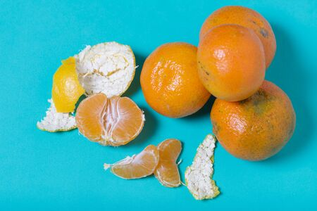 Tangerines are stacked in a pyramid. Next to them is peeled mandarin. Visible slices of mandarin and skin from it. On a mint background. Stock Photo