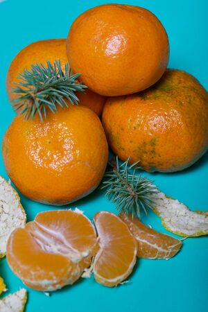 Tangerines are stacked in a pyramid. Next to them is peeled mandarin. Visible slices of mandarin and skin from it. A branch of blue spruce. On a mint background.