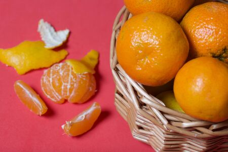Tangerines in a wicker basket. Next to the basket is peeled mandarin. Visible slices of mandarin and skin from it.  Against the background of coral color.