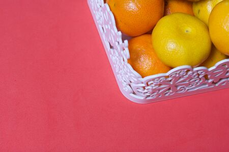 Tangerines in a wicker basket.  Against the background of coral color. Stock Photo