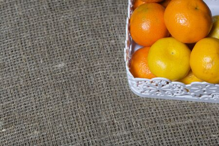 Tangerines in a wicker basket. Against the background of linen fabric.