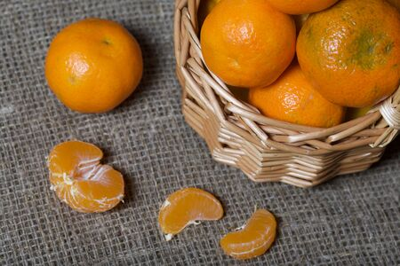 Tangerines in a wicker basket. Next to the basket is peeled mandarin. Visible slices of mandarin and skin from it. Against the background of linen fabric.