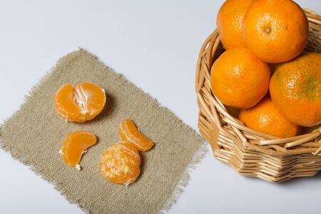Tangerines in a wicker basket. Next to the basket is peeled mandarin on a piece of linen. Visible slices of mandarin. On white background.